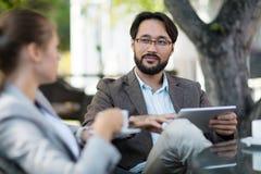 Коллективно обсуждать с коллегой в внешнем кафе Стоковое Изображение