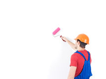 Колеривщик мастера стоит на лестницах с роликом стоковое фото rf