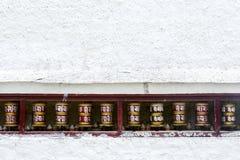 Колеса молитве на белой стене Стоковые Фото