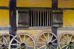Колеса телеги на старой стене самана дома Стоковая Фотография RF