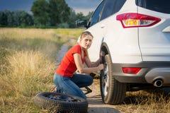 Колесо автомобиля красивой женщины изменяя на throu сельской дороги идя Стоковые Фотографии RF