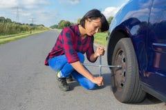 Колесо автомобиля молодой женщины изменяя на проселочной дороге Стоковая Фотография