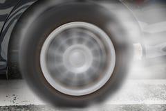 Колесо автомобиля перемещаясь и куря на варианте темноты следа Стоковое Изображение