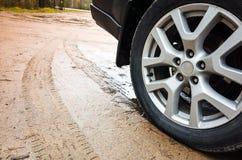 Колесо автомобиля с диском светлого сплава на пакостной проселочной дороге Стоковое Изображение RF