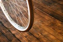 Колесо стильного велосипеда с белой оправой и коричневой резиновой автошины на стильной деревянной предпосылке Стоковое фото RF