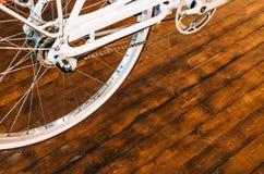 Колесо стильного велосипеда с белой оправой и коричневой резиновой автошины, цепи, звездочки на стильной деревянной предпосылке Стоковое Изображение