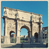 Дуга Константина с Колизеем на предпосылке стоковое фото