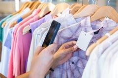 Код штриховой маркировки скеннирования женщины с ее мобильным телефоном Стоковые Фото