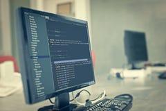 Коды вебсайта на мониторе компьютера на офисе Стоковые Изображения RF