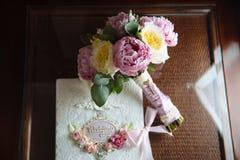 Кольца золота свадьбы и букет цветков на темном деревянном столе Замужество концепции Стоковое Изображение