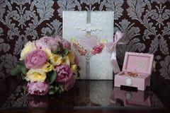 Кольца золота свадьбы и букет цветков на темном деревянном столе Замужество концепции Стоковое фото RF