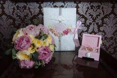 Кольца золота свадьбы и букет цветков на темном деревянном столе Замужество концепции Стоковая Фотография