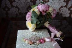 Кольца золота свадьбы и букет цветков на темном деревянном столе Замужество концепции Стоковое Фото