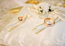 Кольца золота свадьбы на белой подушке Стоковая Фотография RF