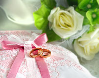 Кольца золота свадьбы на подушке с букетом Стоковые Фото