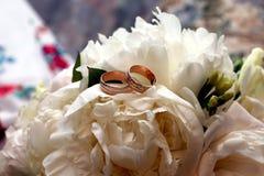 Кольца золота для wedding на букете свадьбы Стоковая Фотография
