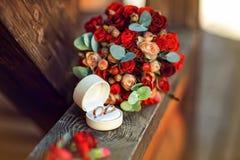 Кольца приближают к красному букету на деревянной предпосылке Стоковое Фото