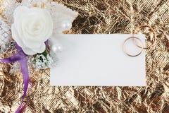 Кольца, цветки и приглашение на предпосылке золота Стоковая Фотография