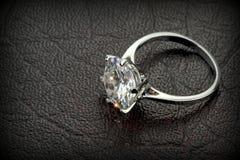 Кольцо пасьянса диаманта на черной кожаной предпосылке Стоковые Изображения RF