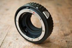 Кольцо расширения для камеры объектива на деревянной предпосылке Стоковое Изображение