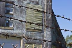 Колючая проволока защищая фабрику Стоковая Фотография