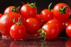 Крайность близкая вверх свежих, органических томатов вишни на черной отражательной предпосылке с waterdrops Крайность близкая вве Стоковые Фото