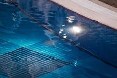 Край бассейна облегченного синью стоковое фото