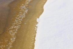 Край воды оранжевого желтого цвета растаял из-под яркого белого стоковые фото