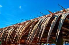 Край крыши покрыт с небом сухих листьев ладони на фоне голубым солнечным стоковое фото rf