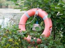 Край оранжевого красного цвета кольца безопасности томбуя жизни озера для тонуть Стоковые Фото