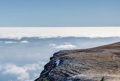 край скалы и белых облаков на голубом небе, стоковая фотография