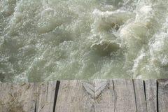 Край старого деревянного моста над изрезанным потоком горы стоковое фото