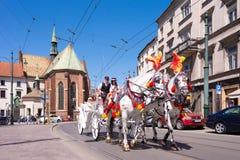 КРАКОВ, ПОЛЬША - ИЮНЬ 2017: Идя туристский экипаж нарисованный белыми лошадями на улице Краков стоковые изображения