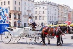 КРАКОВ, ПОЛЬША - ИЮНЬ 2017: Экипажи на главной площади в Краков в летнем дне, Польша лошади стоковые изображения