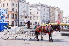 КРАКОВ, ПОЛЬША - ИЮНЬ 2017: Экипажи на главной площади в Краков в летнем дне, Польша лошади стоковые фото