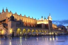 КРАКОВ, ПОЛЬША, 4-ОЕ ИЮЛЯ: Sukiennice - ткань Hall в заходе солнца Стоковые Изображения