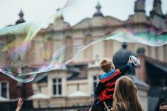 КРАКОВ, ПОЛЬША - 27-ОЕ ИЮНЯ 2015: Мальчик сидя на плечах и касанных гигантских пузырях папы Стоковая Фотография