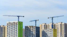 3 крана башни строят дома современные панели Стоковые Изображения RF