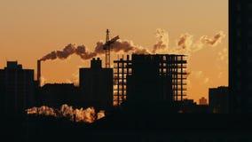 Краны башни силуэта работая на конструкторах строительной площадки жилых работая заход солнца восхода солнца акции видеоматериалы
