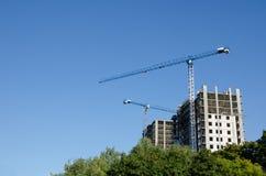 Краны конструкции на предпосылке голубого неба и зеленых деревьев Горизонтальный взгляд Стоковое фото RF