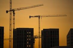 Краны на заходе солнца. Краны индустриального строительства и силуэты здания над солнцем на восходе солнца. Стоковые Изображения RF