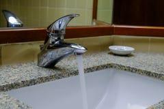 Краны нержавеющей стали раскрывают белые washbasins Стоковая Фотография
