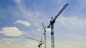 Краны оставаясь все еще на строительной площадке под облачным небом Timelapse видеоматериал