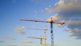 Краны оставаясь все еще на строительной площадке под облачным небом Timelapse сток-видео