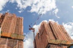 Кран башни на зданиях под конструкцией с защитой Стоковые Фото