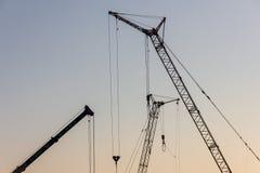 Кран башни на строительной площадке на восходе солнца кливер стоковые фотографии rf