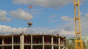 Кран башни поднимает и понижает материалы для строительства на здании акции видеоматериалы