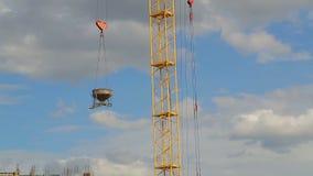 Кран башни поднимает и понижает материалы для строительства на здании видеоматериал