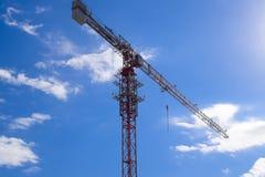 Кран здания башни против голубого неба и солнца Конструкция новых зданий с краном башня крана Стоковые Изображения RF