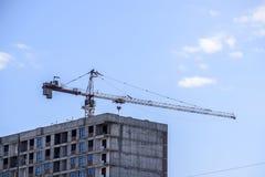 Кран здания башни против голубого неба и солнца Конструкция новых зданий с краном башня крана Стоковые Фотографии RF